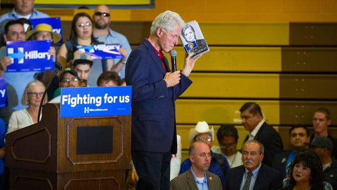 Former United States president Bill Clinton, speaking at a rally Thursday, June 2, 2016, at Picacho Middle School, holds up a copy of a book written by his wife, presidential candidate Hillary Clinton, which he said had been given to him before the rally by a man named Carlos who had it signed by 2,016 Clinton campaign supporters.