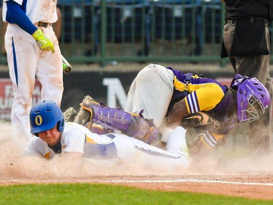 Oxford's Drew Bianco slides underneath Hattiesburg catcher Devin Lang during the 2016 MHSAA state championship.