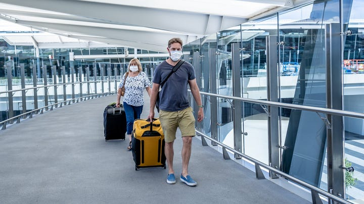 Airport travelers in masks.