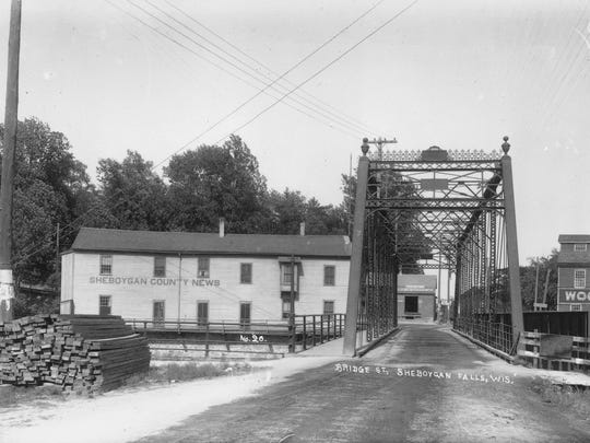 This is the Monroe Street Bridge looking east. The same bridge is seen here looking east past the Sheboygan County News Building, on the left, and Brickner Woolen Mills Warehouse as seen in the background on the right. The river here was first spanned in 1837 to connect the two parts of the village- Rochester and Sheboygan at the Falls. This photo is circa 1905.