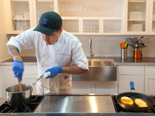 Paco Garcia is a guest chef at MESA in New Albany. Here, he stirs the sauce for his Capirotada (Mexican bread pudding) recipe at MESA. At right, he grills a Mexican bollilo (a crusty bread) for his torts sandwich.  Feb. 19, 2018