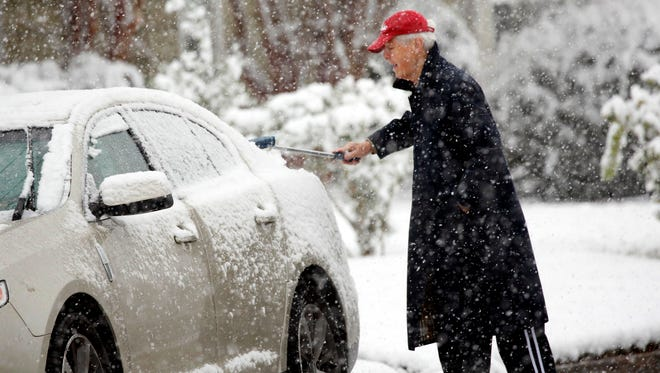A Jackson, Miss., resident wipes snow off the windows of a vehicle as a heavy morning snow falls. The forecast called for a wintry mix of precipitation across several Deep South states.
