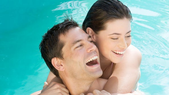 A couple embracing in a pool on a clothing-optional