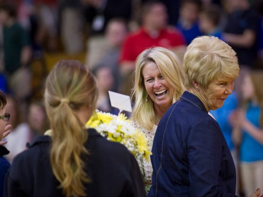 Thompkins Middle School teacher Tonya Weinzapfel is greeted with flowers and family, including son Reid, 12, left, Kendyl, 16, and her mom, Ann Williams, right, during a surprise assembly to announce her selection as the Middle School Teacher of the Year Wednesday morning.