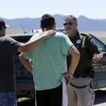 A Montana Highway Patrol deputy talks with family members at the scene of a shooting in Pryor on Wednesday. The FBI confirmed that two people were killed and a third injured.