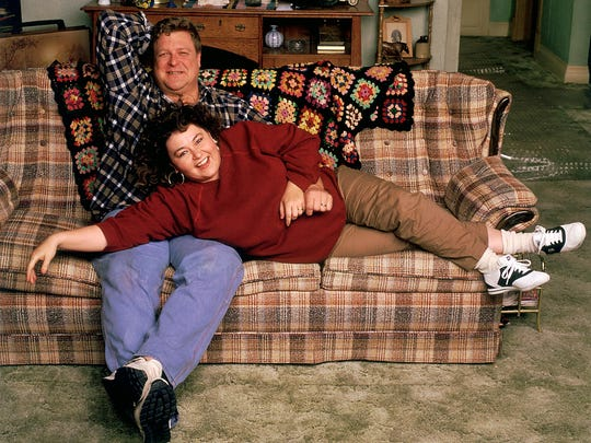 "John Goodman, sitting up, and Roseanne Barr get comfortable on the iconic ""Roseanne"" couch."