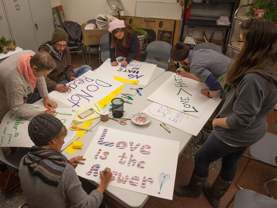 Demonstrators prepare signs Wednesday night at the