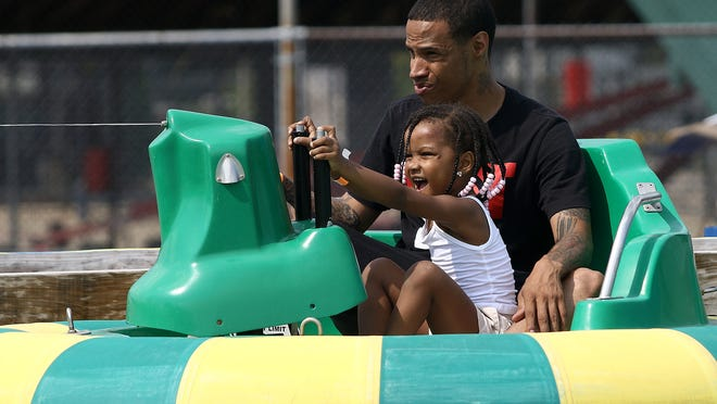 Janiya Williams, 3, of Canton presses the button to squirt water from the motorized tube ride she is sharing with her father, Janairul Williams, on Sunday afternoon at the Funtimes Fun Park.