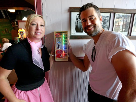 "Trudi and Evan Schmidt show off the ""True Love!"" rating that they earned on the KissMeter at Mac's Place in Silverton. Invented by Stu Rasmussen, the coin-operated machine measures the intensity and duration of a couple's kiss."