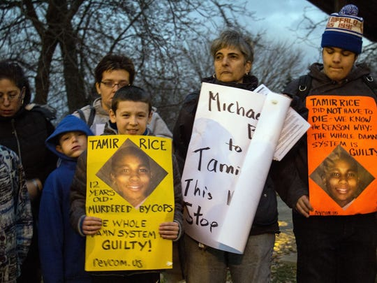Young protesters display signs featuring Tamir Rice's face on Monday, Nov. 24, 2014, at Cudell Commons Park in Cleveland during a rally for Rice, a 12-year-old boy who died Sunday after being shot by police. Cleveland police defended the conduct of the officer who fatally shot the boy, who was wielding a fake handgun.