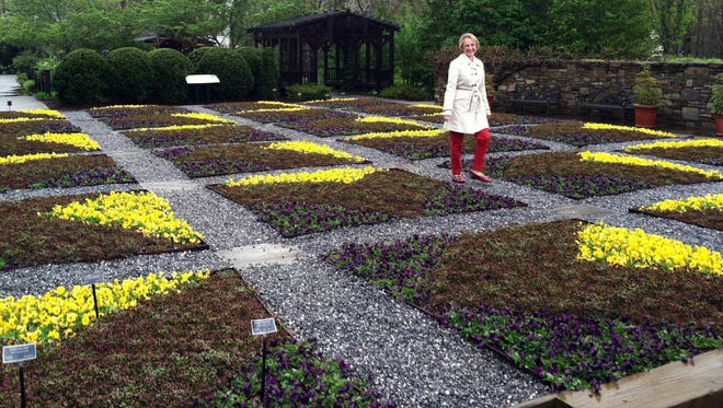 Clara Curtis, director of design and education at the North Carolina Arboretum in Asheville, walks in the arboretum's quilt garden. The garden is planted each year in the design of a traditional quilt block pattern to connect the garden to the region's Southern Appalachian heritage.