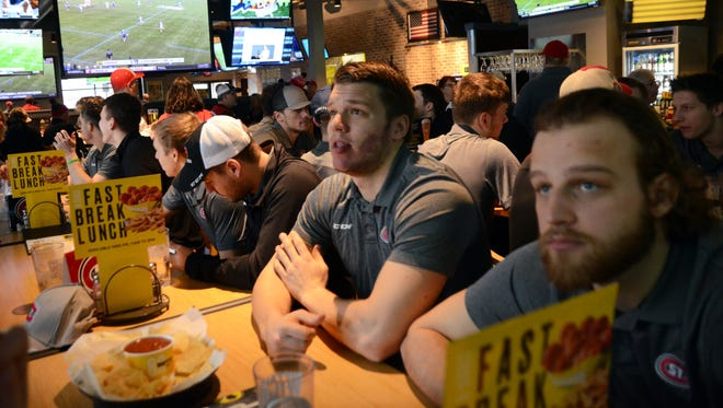 St. Cloud State men's hockey players await the start of the NCAA Division I selection show on Sunday at Buffalo Wild Wings. The Huskies were named the No. 1 overall seed for the tournament.