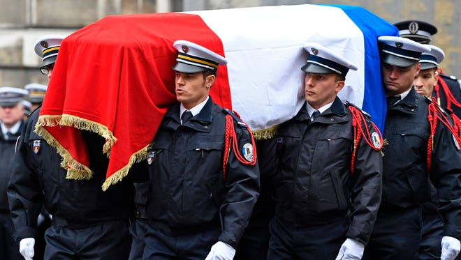 French police officers carry the flag-draped casket during a ceremony honouring the policeman killed by a jihadist in an attack on the Champs Elysees, on April 25, 2017 at the Paris prefecture building.