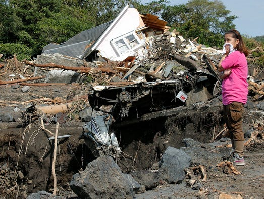 Yu Kosaka searches for friends of her parents on Oct. 18 after a mudslide triggered by Typhoon Wipha destroyed homes on Oshima Island, Japan. Twenty-three people were killed and 26 others are missing after the Oct. 16 storm swept through northeastern Japan.