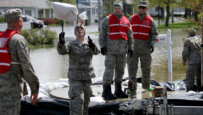 Members of the 174th Air National Guard work to sandbag a sewage pumping station an Greig Road in Sodus Point. The road has been closed due to flooding.
