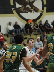 Oak Park's Riley Battin, center, eyes the basket as Tyler Garcia of Royal defends during Friday night's game.