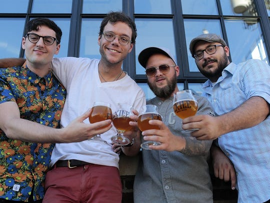 (Left to right) Greg Wheeler, of the band The Wheelers, Christopher Ford, of Chris the Conquered, Dustin Smith and Andy Poppen, of The Maytags, pose for a photo holding glasses of the Daytrotter beer on July 19, 2015 at Exile Brewing Company in Des Moines, IA. Daytrotter is the website for the recording studio Horseshack located in Rock Island, Illinois. The studio is a place where popular artists as well as up-and-coming artists record. The Daytrotter beer by Exile was inspired by the music website.