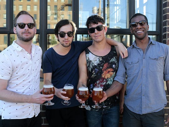 (Left to right) Neil Robertson, Russ Ault, Joshua Novak, and Jeremiah Mora, of the band Oko Tygra, pose for a photo holding glasses of the Daytrotter beer on July 19, 2015 at Exile Brewing Company in Des Moines, IA. Daytrotter is the website for the recording studio Horseshack located in Rock Island, Illinois. The studio is a place where popular artists as well as up-and-coming artists record. The Daytrotter beer by Exile was inspired by the music website.