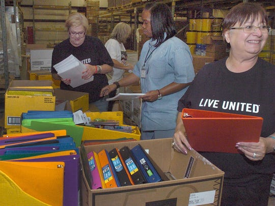 "St. Landry-Evangeline United Way volunteers Friday sort through school supplies collected from the annual ""Stuff the Bus"" effort."
