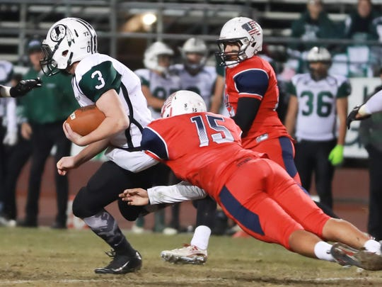 Tulare Western linebacker Julian Trevino (15) tackles Tehachapi's Connor Timm during Thursday's Central Section Division III quaterfinal playoff game at Bob Mathias Stadium.