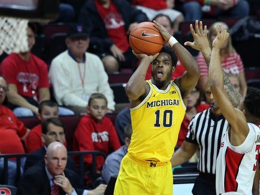 Michigan guard Derrick Walton Jr. (10) shoots as Rutgers guard Corey Sanders (3) defends during the first half of an NCAA college basketball game Wednesday, Feb. 22, 2017, in Piscataway, N.J. (AP Photo/Mel Evans)
