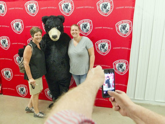 Ann Kramer, left, of Battendorf, Iowa, and Jennifer Kramer, of Los Angeles, pose for a picture with Boomer, Cherry Republic's mascot, on a tour through the company's production facility during a cherry orchard tour.