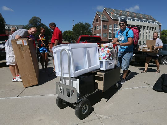 DMACC student Brett Osterman of Dows, right, helps his sister Molly move into Maple Hall at Iowa State University Tuesday. Behind Brett is his mother Molly, who has helped three of her children move into college this week.