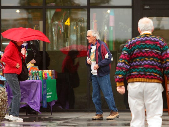 A woman carries a red umbrella, matching her red jacket, while walking past Girl Scouts selling cookies in front of the Jensen's grocery store in Palm Springs Sunday afternoon, as a steady rain blanketed the valley.