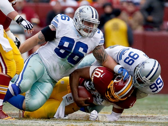 Washington Redskins quarterback Robert Griffin III (10) is sacked by Dallas Cowboys defensive tackle Nick Hayden (96) and defensive end George Selvie (99) during the second half of an NFL football game in Landover, Md., Sunday, Dec. 28, 2014. (AP Photo/Alex Brandon)