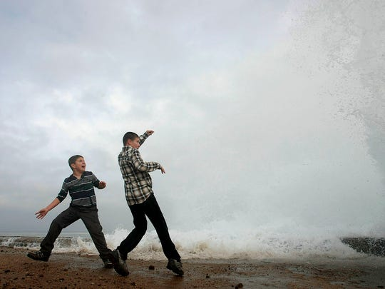 Aidan Stephenson,12, and Conor Stephenson,10, visiting from Phoenix, watch the waves breaking on the rocks on Ocean View Blvd., Wednesday, Dec.10, 2014, in Pacific Grove, Calif. Northern California residents are bracing for a powerful storm that could be the biggest in five years and which prompted the National Weather Service to issue a high wind and flash flood warning. The storm is expected to arrive Wednesday and pelt the region through Thursday. (AP Photo/Monterey Herald, Vern Fisher)