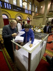 Workers unload budget bills that will be distributed to members' desks in the Assembly Chamber at the Capitol on Tuesday in Albany, as lawmakers readied tovote on the final provisions of the state budget.