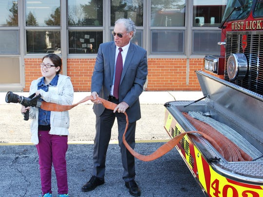 Pataskala Mayor Mike Compton helps Gabriela Pablo hold a fire hose as part of her superintendent for the day duties.