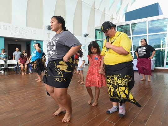 Cultural dance instructor Bobbie Tainatongo, right, helps a young participant learn dance steps during Nihi ta Fan Baila at the Guam Museum on Feb. 10, 2018.