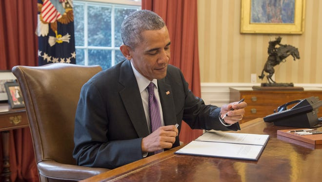 President Obama signs a presidential memorandum on paid leave for federal employees, in the Oval Office Thursday.