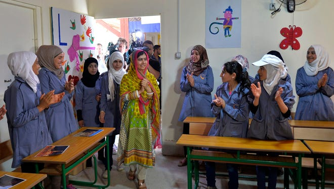 Pakistani Nobel Peace Prize laureate Malala Yousafzai, center, is applauded July 12, 2015, by Syrian refugees on her 18th birthday as she visits the school for girls her foundation built in Lebanon's Bekka Valley.