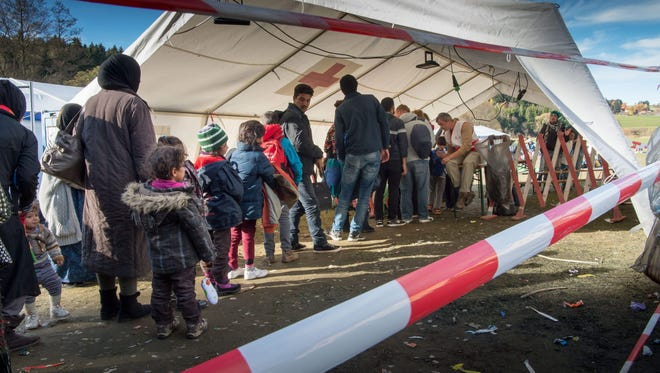 Refugees and migrants stand in line to draw a number and to cross the German-Austrian border near the border town of Hanging, Austria,  in November.