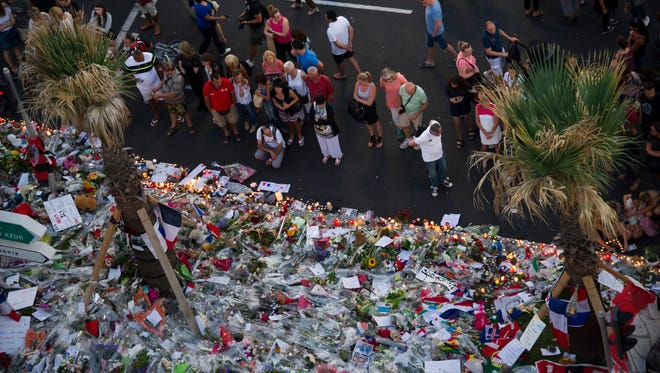 People gather at a makeshift memorial of flowers and candles on July 17, 2016, on the Promenade des Anglais, where a truck crashed into a crowd during  Bastille Day celebrations in Nice, France, killing 84.