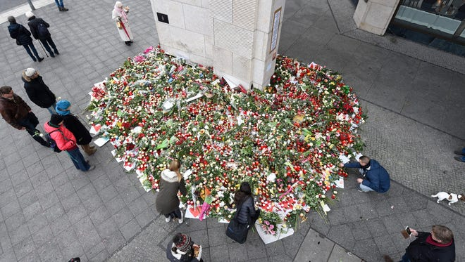 Visitors stop at an impromptu memorial of candles and flowers at the Breitscheidplatz Square Christmas Market in Berlin on  Dec. 22, 2016.