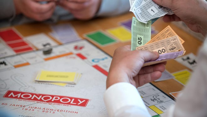 A player holds toy money while fighting for supremacy on a 'Monopoly' game board during the final of the German Monopoly Championships in Berlin in 2015.