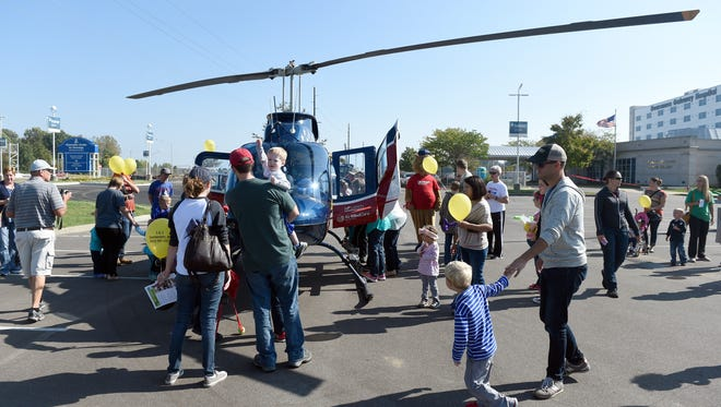 Kids and their parents check out the Air Evac helicopter after it flew in for the 4th annual Trucks and Heroes event at Deaconess Gateway Hospital in Newburgh Saturday.  The event presented by SMILE on Down Syndrome allowed kids to explore emergency and work vehicles that they would normally see from a distance and meet the individuals who operate them.