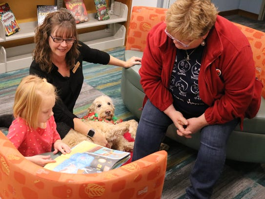 Jane and Erin Sandvick, left, read to Bobbi Beck, right, and her therapy dog, Poppy, during the 'Barking for Books' program at the Marblehead Peninsula Branch Library.