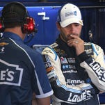 Jimmie Johnson (right) stands in the garage with crew chief Chad Knaus during Friday's practice for the Sprint Cup Series race at Michigan International Speedway. Johnson is supporting NASCAR's rule addition that bars drivers from approaching the track or moving cars after an incident during the race.