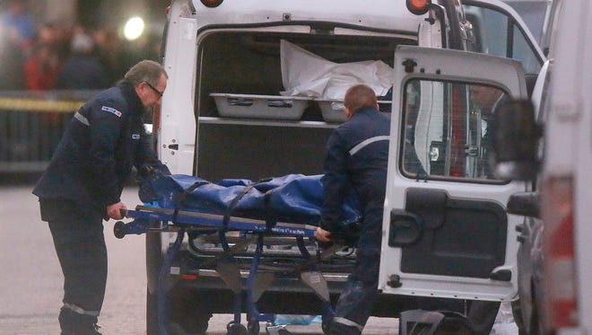 Two men carry a  body into a hearse after an intervention of security forces against a group of extremists in Saint-Denis, near Paris, Wednesday, Nov. 18, 2015. A woman wearing an explosive suicide vest blew herself up Wednesday as heavily armed police tried to storm a suburban Paris apartment where the suspected mastermind of last week's attacks was believed to be holed up, police said.