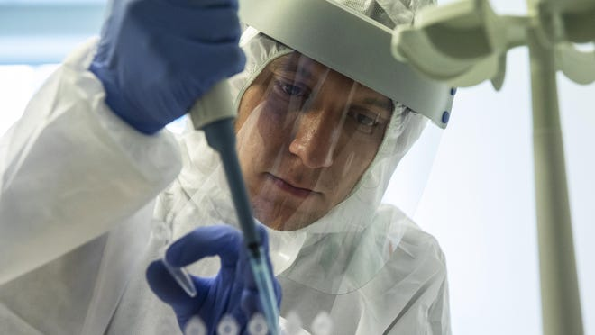 A medical worker performs a COVID-19 test at a test center at Vnukovo airport outside Moscow, Russia, Friday, Aug. 7, 2020. Authorities in Russia say they are about to approve a COVID-19 vaccine, with mass vaccinations planned as early as October 2020, using shots that are yet to complete clinical trials. But scientists worldwide are sounding the alarm that the headlong rush could backfire and point to ethical issues that undermine confidence in the Russian studies.