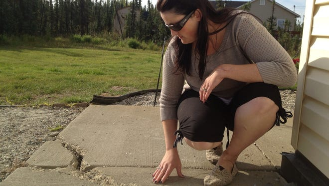 Cathy Richard of North Pole, Alaska, shows how her sidewalk cracked because it's built on permafrost -- land that freezes and thaws each year on its top layer.