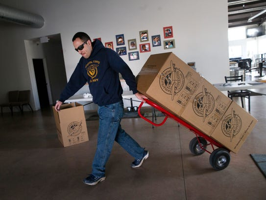 Randy Willard moves boxes filled with Christmas gifts Monday at the Calvary Chapel in Farmington.