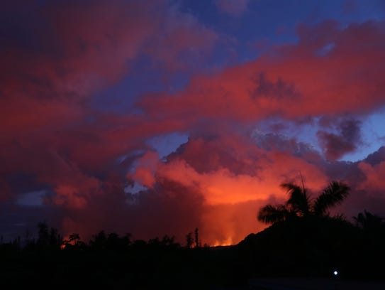 Lava from Kilauea volcano lights up the evening sky