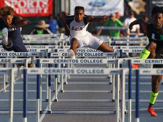 At center, La Quinta High School senior Koty Burton won titles in both the 110-meter hurdles and the 300-meter hurdles, including an impressive last few meters of the 110's, pictured here, where he came from behind Upland junior Joseph Anderson, at far right,  to edge him at the line with a time of 14.06 seconds to Anderson's 14.08.
