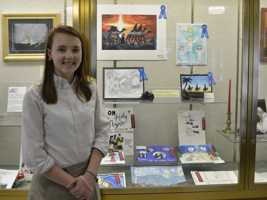Kristen Landsman stands by a showcase of the artwork submitted for the Diocese of Harrisburg's Christmas Card Contest.