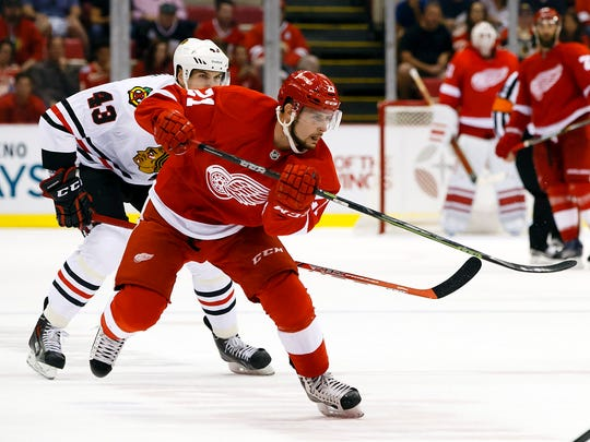 Detroit Red Wings left wing Tomas Tatar (21) takes a shot on an open net to score a goal for a hat trick in the third period against the Chicago Blackhawks at Joe Louis Arena on Sept. 23, 2015.
